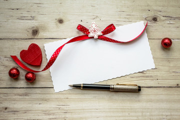 Valentine card with red heart and pen over wooden background