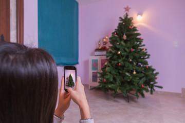 woman photographing Christmas tree