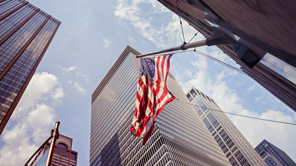 Vintage toned American flag and skyscrapers in NYC.
