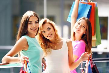 Beautiful young women with shopping bags in shopping center