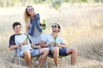 People laugh and drink beer in nature