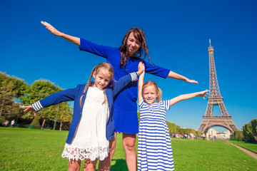 Happy family in Paris near Eiffel tower. French summer holidays, travel and people concept