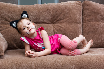 little girl with cat face painting on couch