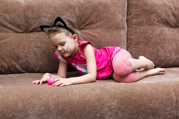 little girl with cat face painting play ball on couch