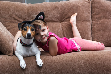 little girl with cat face painting embrace her dog