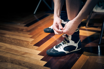 Closeup of young boxer's hands tying trainers on parquet background