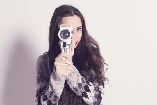 Beautiful modern girl recording with a very old and dirty super 8mm camera