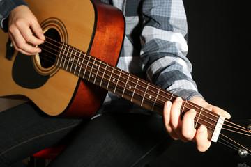 Guitarist plays guitar in dark studio, close up