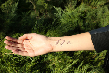 Female hand with tattoo on green background
