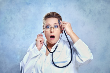 Shocked female doctor listening her mind with stethoscope.