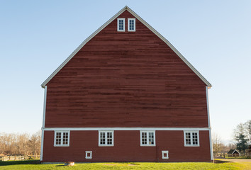 Unique red barn with green grass and blue sky
