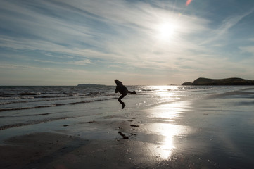 a man gives a kick while jumping on the beach at sunrise