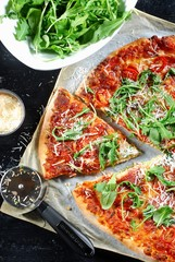 Pizza with cherry tomatoes, ham and arugula sprinkled with cheese, on parchment paper on black wood, with a bowl of arugula and a pizza knife