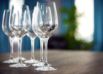 Empty wine glasses on wooden table against blurred background