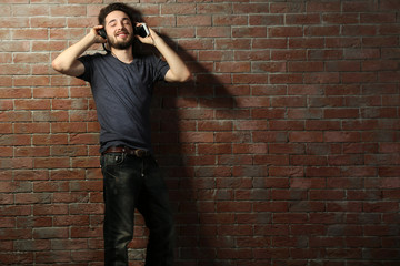 Young handsome man listening music with headphones on brick wall background