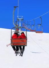 Skiers couple on ski lift against winter snowy mountain landscap