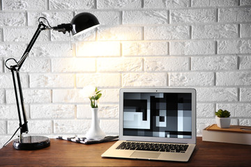 Modern lamp and laptop on table on brick wall background