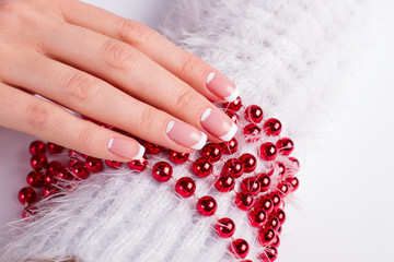 Fototapete - Beautiful festive french manicure on red beads.