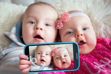 Twins taking selfie with a cell phone camera
