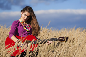 20-25 years old country girl holding a guitar in field against blue cloudy sky background