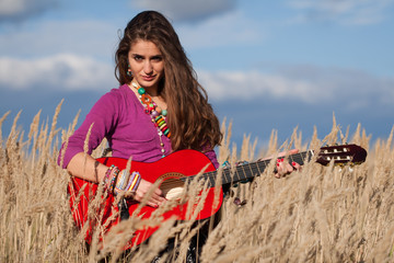 Young country woman playing guitar in field against blue cloudy sky background