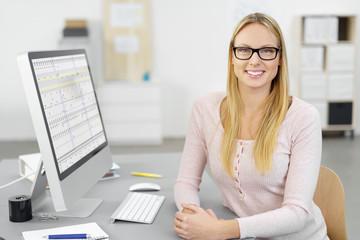 motivierte mitarbeiterin sitzt am schreibtisch im büro mit tabellen auf dem monitor
