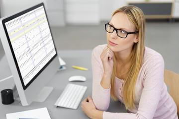 frau sitzt am computer und schaut konzentriert nach oben