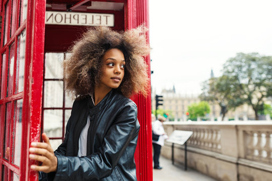 Young woman portrait close to red telephone box in London.