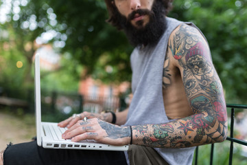 Young tattooed man portrait using laptop in Shoreditch borough.