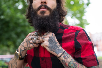Hands close up of young tattooed man portrait in a park. Shoreditch borough. London.
