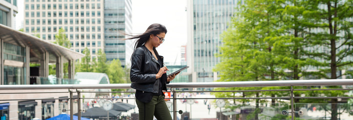 Panoramic image of young mixed race businesswoman portrait outdoors in Canary Wharf in London.