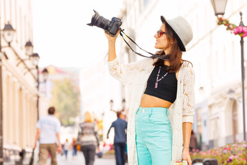Girl wearing sunglasses shooting with camera