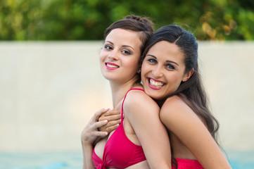 Two girlfriend portrait in swimming pool.