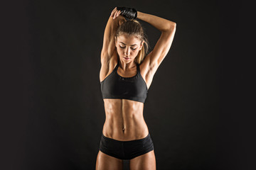 Young sporty woman portrait doing stretching against black background.
