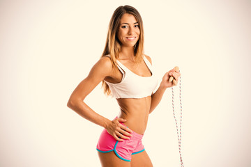 Beautiful fitness woman with jump rope, studio portrait.