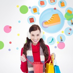 Composite image of brunette in winter clothes holding bags
