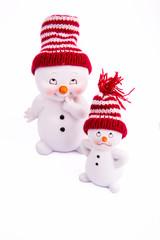 Два белых снеговика в шапках на белом фоне