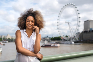 Young woman portrait in London on Westminster bridge. London Eye in the background.