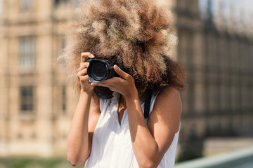 Young woman with camera taking photos in London on Westminster bridge.