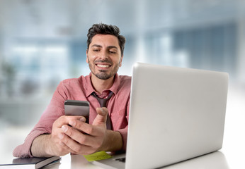 happy attractive businessman working at office desk using mobile phone