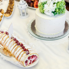Delicious wedding cake with green and white flowers on it.  Tasty baking, banquet table.