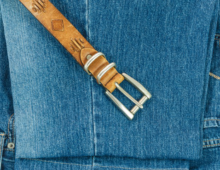 Vintage leather belt with buckle on old blue jeans background