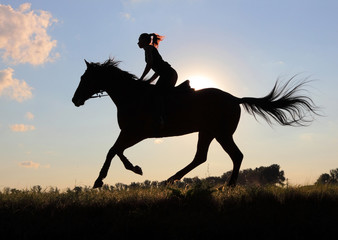 Equetsrian riding her horse at sunset