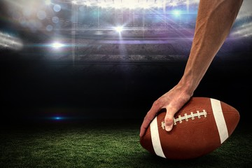 Composite image of american football player placing the ball
