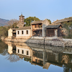 Ancient white Chinese house reflected in a tranquil canal, Hengdian, China
