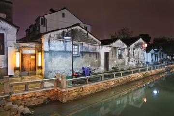 Waterway in traditional neighborhood at night, Suzhou, China