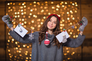 Attractive positive young woman holding handmade christmas decoration