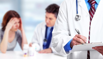 Doctor hands writing on a clipboard.