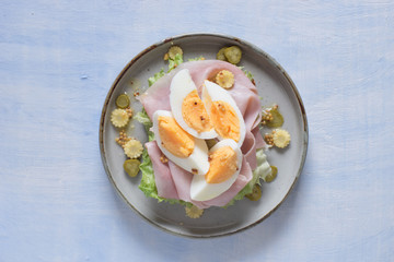 Open sandwich with salad, prosciutto cotto, pickles, corn and boiled egg