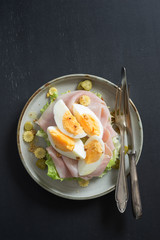 Scandinavian open sandwich with salad, prosciutto cotto, pickles, corn and boiled egg on dark background